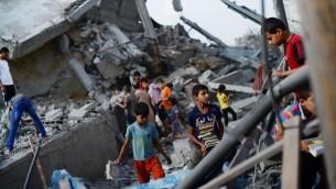 اطفال فلسطينيون يساعدون في البحث عن الكتب الدينية  في المسجد الذي استهدفه القصف الجوي الاسرائيلي في النصيرات في وسط قطاع غزة، في وقت مبكر من 10 أغسطس  2014. AFP PHOTO / ROBERTO SCHMIDT