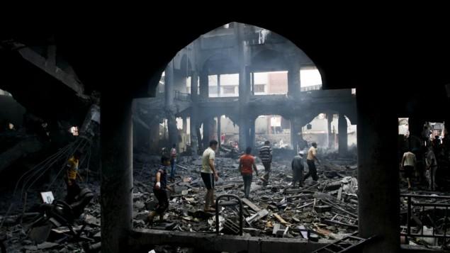 فلسطينيون يتفقدون أنقاض مركز تسوق دمر في اعقاب غارة اسرائيلية ليلية، مدينة غزة جنوب مدينة رفح، 24 أغسطس 2014 Abed Rahim Khatib/Flash90