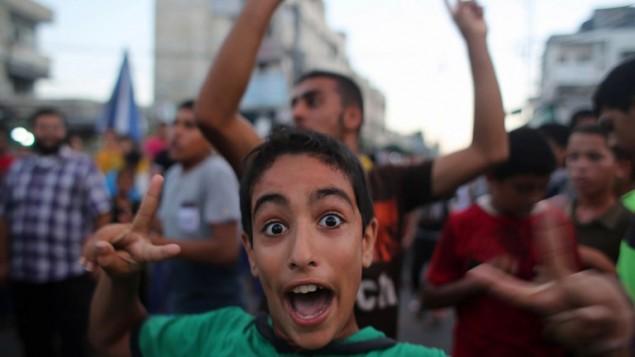 صبي فلسطيني في شوارع رفح  اثناء الاحتفال بالتوصل الى اتفاق بين حماس واسرائيل بعد سبعة أسابيع من القتال، الثلاثاء 26 أغسطس، 2014   AFP/SAID KHATIB