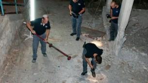 خبراء المتفجرات اثناء جمع بقايا صاروخ اطلق من جنوب لبنان على إسرائيل، وهبط في الجليل الغربي، شمال اسرائيل. 23 أغسطس 2014.  Ayal Margolin/Flash90