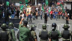فلسطينيون خلال مظاهرة تأييد لحماس يلقون الحجارة باتجاه قوات الأمن الفلسطينية والتي اغلقت الطريق إلى نقطة تفتيش إسرائيلية في وسط مدينة الخليل بالضفة الغربية  22 أغسطس 2014   AFP/ Hazem Bader