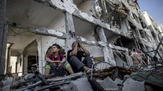 أخوان فلسطينيان يجلسان على أنقاض بيتهم في بيت حانون 5 أغسطس 2014 (AFP/MARCO LONGARI)