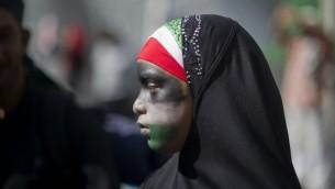 صورة توضيحية, فتاة محجبة رسمت على وجهها الوان العلم الفلسطيني تشارك في مظاهرة مضادة لاسرائيل في كيب تاون جنوب افريقيا 9 اغسطس 2014 (أ ف ب)