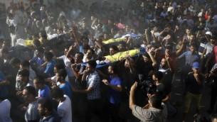 تشييع جنازة أربعة أولاد، من عائلة بكر، في مدينة غزة، 16 يوليو، 2014. أربعة قتلوا وأصيب عدد آخر بجروح في مخيم الشاطئ في غزة في قصف اسرائيلي  AFP/MOHAMMED ABED