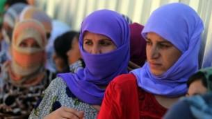 نساء يزيديات عراقيات يقفن من أجل الحصول على الطعام في مخيم بالقرب من  نهر دجلة في محافظة دهوك غرب كردستان، حيث لجأوا بعد فرارهم من الدولة الإسلامية 13 أغسطس 2014  AFP/AHMAD AL-RUBAYE