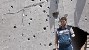 أحمد عياد  أمام شظايا ملحوظة على منزله في حي الشجاعية في مدينة غزة  30 أغسطس 2014 اصيب احمد بقذيفة دبابة اسرائيلية مما ادى الى قطع  ذراعه وقتل أربعة من أفراد أسرته. AFP PHOTO / ROBERTO SCHMIDT