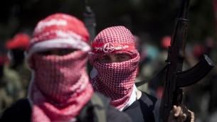 مسلح ملثم من الجبهة الشعبية لتحرير فلسطين،  2 سبتمبر 2014 في مدينة غزة خلال مسيرة للاحتفال بعد اسبوع من وقف إطلاق النار AFP/MAHMUD HAMS