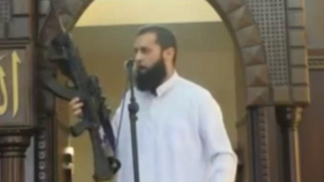 Screenshot from MEMRI video of Gaza imam brandishing rifle during a sermon on Augusyt 29, 2014.