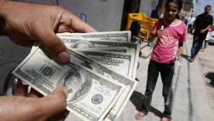 رجل فلسطيني يعمل في خدمة السلطة الفلسطينية يعرض اموالا (دولار) قام بسحبها من بنك فلسطين في رفح, جنوب غزة  8 يونيو 2012  (عبد الرحيم خطيب/ فلاش 90)