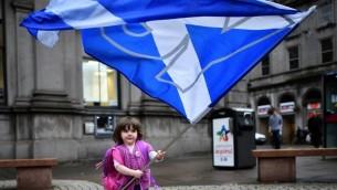 طفلة تحمل علم تأييد الاستقلال في شوارع أبردين في اسكتلندا, سبتمبر 15. 2014    BEN STANSALL/AFP