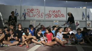 """الحاجز الفاصل في بيت شيمش، 02 سبتمبر، 2014. على الجدار مكتوب """"الجدار الفاصل، وصمة عار للصهيونية"""".  Nati Shohat/Flash90"""