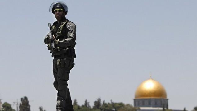 شرطي إسرائيلي يقف على سطح مبنى أمام قبة الصخرة في القدس الشرقية  4 يوليو 2014 (أحمد الغرابلي / أ ف ب)
