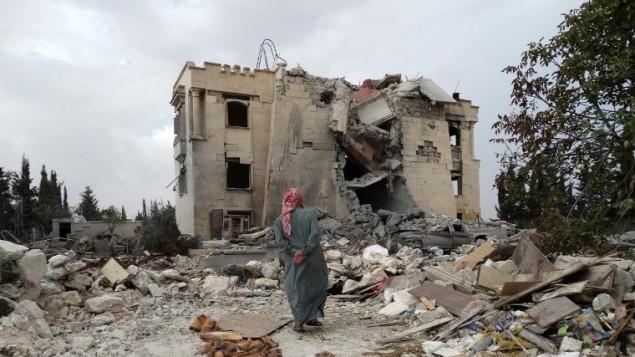 رجل سوري يتفقد الأضرار بعد غارة جوية شنها التحالف بقيادة الولايات المتحدة ضد  مقر جبهة النصرة، 20 كم شمال مدينة حلب  25 سبتمبر 2014  AFP/Sami Ali
