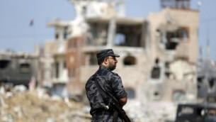 رجل من قوات امن حماس في انتظار وصول رئيس الوزراء رامي حمد الله  خلال جولة لبعض المناطق الأكثر تضررا من حرب ال 50 يوما بين اسرائيل وقطاع غزة في شهري يوليو وأغسطس، حي الشجاعية مدينة غزة،  9 أكتوبر، 2014  Mohammed Abed/AFP