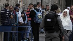 14 أكتوبر 2014 شرطي اسرائيلي يمنع امرأة مسلمة من الدخول الى المسجد الاقصى وفقا للتقيدات في الدخول بعد الاشتباكات التي دامت طوال اسبوع  AFP PHOTO/ AHMAD GHARABLI