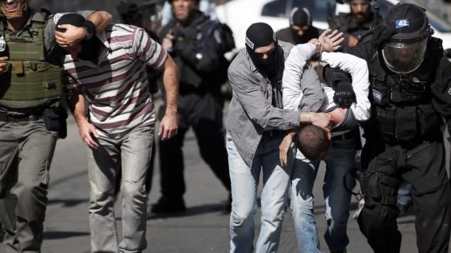 قوات الأمن الإسرائيلية تعتقل شابا فلسطينيا خلال اشتباكات بعد صلاة الجمعة في القدس الشرقية  24 تشرين الأول، 2014. AFP PHOTO / THOMAS COEX