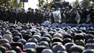 قوات الأمن الإسرائيلية تقف أمام المصلين المسلمين الفلسطينيين وهم يؤدون صلاة الجمعة التقليدية في شارع خارج البلدة القديمة في القدس الشرقية  24 تشرين الأول 2014   AFP PHOTO / THOMAS COEX