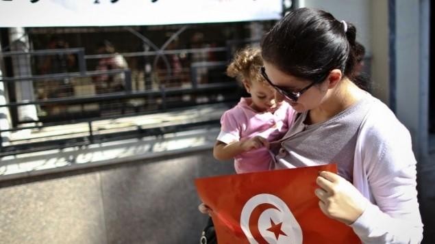 تونسية في مصر تغادر السفارة التونسية في القاهرة بعد الادلاء بصوته في الانتخابات البرلمانية  25 أكتوبر 2014.AFP PHOTO / MOHAMED EL-SHAHED