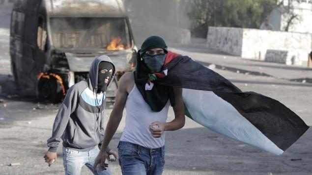ملثم فلسطيني يلقي حجارة أثناء اشتباكات مع قوات الأمن الإسرائيلية في القدس الشرقية، 30 أكتوبر 2014 AFP/Ahmad Gharabli