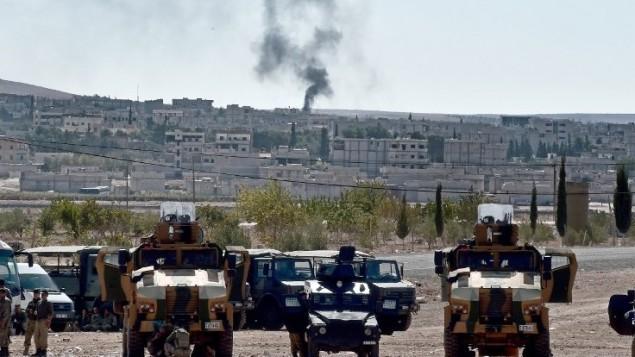 الدخان يرتفع من البلدة السورية عين العرب،  5 أكتوبر 2014.  AFP PHOTO / ARIS MESSINIS