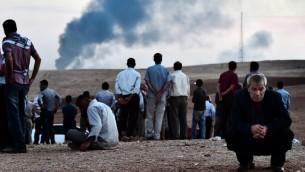 سكان بلدة كوباني الاكراد عند الحدود التركية السورية كما يعلو الدخان من عين العرب، والمعروفة باسم كوباني  9 أكتوبر 2014.  AFP PHOTO / ARIS MESSINIS