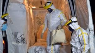 مسعفون يرتدون الملابس الواقية من الخطر البيولوجي لنقل المريض الغيني المشتبه بانه يحمل مرض إيبولا في البرازيل، 10 أكتوبر، 2014.   AFP PHOTO/LUIZ CARLOS CRUZ