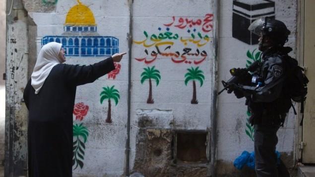 امرأة فلسطينية تصرخ في وجه رجل شرطة إسرائيلية في البلدة القديمة في القدس  30 أكتوبر عام 2014 بعد ان اغلقت السلطات الإسرائيلية مؤقتا باحة المسجد الاقصى، ثالث أقدس موقع في الإسلام AFP PHOTO/ AHMAD GHARABLI