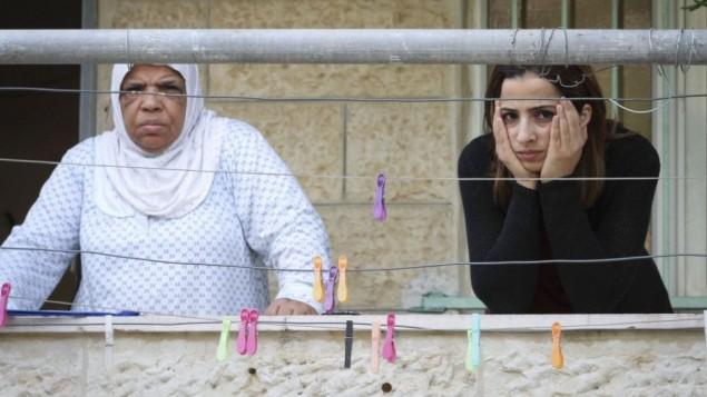 نساء فلسطينيات يطلن على البيوت التي دخلها المستوطنون 30 سبتمبر 2014 (فلاش 90/ سليمان خضر)