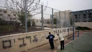 """عمال ينظفون جرافيتي """"الموت للعرب"""" و """"صدق كهانا"""" في المدرسة اليهودية عربية في القدس فبراير 7, 2014 (فلاش 90)"""