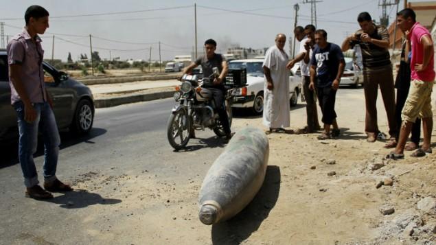 فلسطينيون ينظرون الى ذخيرة غير منفجرة في شارع في دير البلح في وسط قطاع غزة  01 أغسطس 2014 Mostafa Ashqar/FLASH90