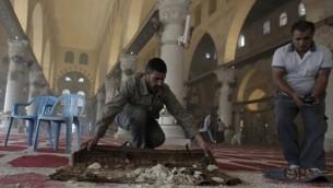 فلسطينيون ينظفون الحطام داخل المسجد الأقصى،  5 نوفمبر 2014 عقب اشتباكات بين رماة الحجارة الفلسطينيين وقوات الأمن الإسرائيلية AFP PHOTO/AHMAD GHARABLI