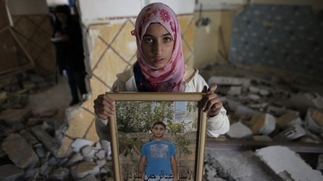 أحد أقارب عبد الرحمن الشلودي وهو فلسطيني قتل اثنين من الاسرائيليين مع سيارته الشهر الماضي، تحمل صورة له داخل منزل عائلته  في شرقي القدس حي سلوان بعد ان هدمت السلطات الاسرائيلية المنزل. 19 نوفمبر 2014   AFP PHOTO/AHMAD GHARABLI