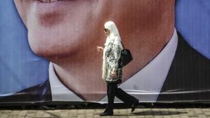 8 أغسطس 2014  امرأة  تمشي امام صورة حملة رئيس الوزراء التركي رجب طيب أردوغان في اسطنبول  AFP PHOTO/OZAN KOSE