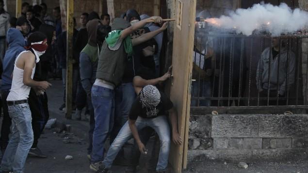 شبان فلسطينيون ملثمون يشتبكون مع قوات الأمن الإسرائيلية في مخيم شعفاط للاجئين الفلسطينيين في القدس الشرقية،  6 نوفمبر 2014.AFP PHOTO/ AHMAD GHARABLI