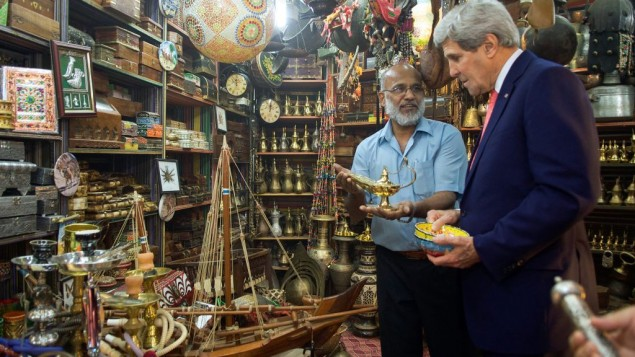 تاجر يعرض مصباح على وزير الخارجية الامريكية جون كيري  اثناء زيارته لسوق مطرح في مسقط، سلطنة عمان، 10 نوفمبر 2014 State Department