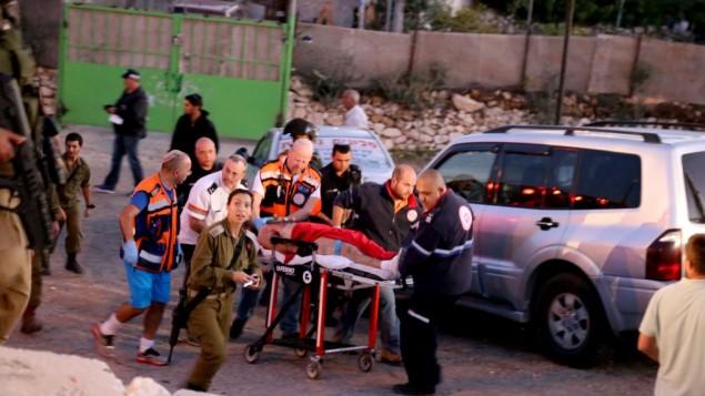 عناصر الأمن والانقاذ الاسرائيلية  مع منفذ عملية الطعن امام محطة للحافلات عند مدخل مستوطنة  ألون شفوت في الضفة الغربية  10 نوفمبر، 2014 Gershon Elinson/Flash90