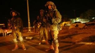 جنود إسرائيليون ينظر عند مدخل قرية فلسطينية العروب، الضفة الغربية، حيث أصيب ثلاثة جنود إسرائيليين بعد ان دهسهم سائق فلسطيني بسيارته على مقربة من مفرق غوش عتصيون، خارج القدس، 5 نوفمبر 2014. Nati Shohat/Flash90