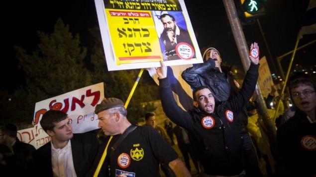 """رجل يحمل لافتة """"كاهانا كان على حق"""" في موقع الهجوم  في القدس 5 نوفمبر، 2014.Yonatan Sindel/Flash90"""