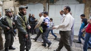 فلسطينيون في  طريقهم إلى المسجد الأقصى في مجمع الحرم القدسي الشريف لأداء صلاة الجمعة، والشرطة الاسرائيلية تراقب الاوضاع  14 نوفمبر 2014  (Yonatan Sindel/Flash90)