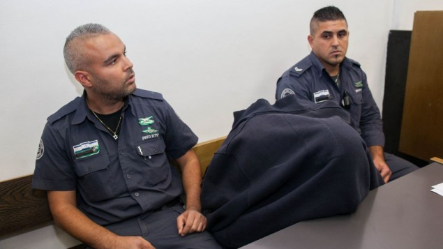 شرطي حرس الحدود المتهم بإطلاق النار وقتل فتى فلسطيني في سن المراهقة   15 مايو في بيتونيا خلال مظاهرات يوم النكبة. الشرطي في الوسط مغطيا وجهه في  المحكمة  في القدس 23 نوفمبر، 2014. (فلاش 90)