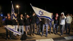 نشطاء يهود يمينيين يحملون العلم الإسرائيلي  بالقرب من الموقع الذي قتلت به شابة يهودية  في هجوم طعن في محطة للحافلات عند مدخل مستوطنة  ألون شفوت بالضفة الغربية، 10 نوفمبر 2014.Nati Shohat/Flash90