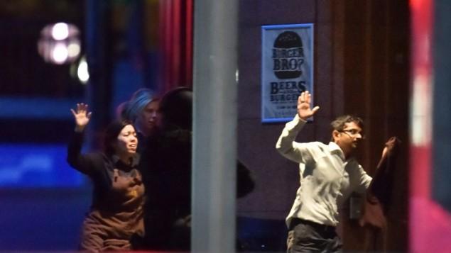 الرهائن يركضون نحو الشرطة من مقهى في سيدني في 15 ديسمبر، 2014AFP/Peter PARKS