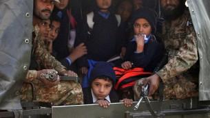 جنود باكستانيون ينقذون اطفال من موقع هجوم شنه مسلحون من طالبان على مدرسة في بيشاور  16 ديسمبر 2014. حيث قتل 130 شخصا على الاقل في هجوم لطالبان على مدرسة يديرها الجيش في شمال غرب باكستان. AFP PHOTO / A MAJEED