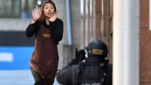أحد الرهائن تركض  نحو الشرطة من مقهى في سيدني في 15 ديسمبر، 2014 AFP/SAEED KHAN