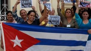 كوبيون يحتفلون مع العلم الوطني في كماغويه، 600 كلم شرق هافانا17 ديسمبر  2014، بعد إطلاق سراح واشنطن ثلاثة جواسيس كوبيين الذين كانوا في سجن أمريكي منذ عام 2001 AFP PHOTO / AIN - ROBERTO MOREJON