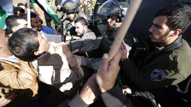 """شرطي الحدود الاسرائيلي """"يخنق"""" زياد أبو عين المسؤول الفلسطيني خلال مظاهرة في الضفة الغربية يوم الأربعاء 10 ديسمبر، 2014 AFP/ABBAS MOMANI"""