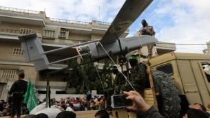 عناصر من كتائب القسام، الجناح المسلح لحركة حماس، يعرضون طائرة بدون طيار خلال  الذكرى السنوية ال27 لتأسيس الحركة الإسلامية  14 ديسمبر 2014 في مدينة غزة AFP/MAHMUD HAMS