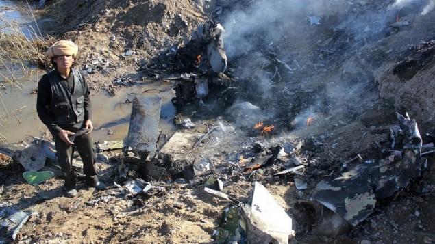 24 ديسمبر 2014 مقاتل الدولة الإسلامية يجمع قطع من بقايا طائرة حربية أردنية في منطقة الرقة في سوريا. اسرت  الدولة الإسلامية طيار أردني بعد اسقاط طائرته الحربية . AFP PHOTO / RMC / STR