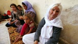 عائلة ايزيدية عراقية  فرت من العنف في بلدة سنجار شمال العراق، يحتمون في مدرسة بالمدينة الكردية دهوك في إقليم كردستان 5 أغسطس 2014. AFP/SAFIN HAMED