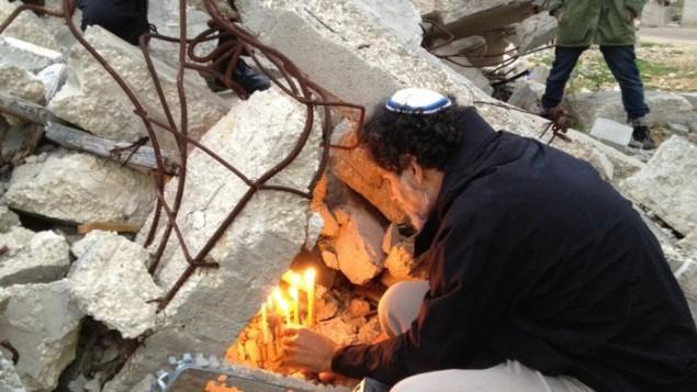 الحاخام اريك اشرمان رئيس جمعية حاخامات من اجل حقوق الانسان يضيء شمعدان فوق حطام بيت فلسطيني هدمته اسرائيل في قرية ديرات جنوب الضفة الغربية 22 ديسمبر 2014 (بعدسة الحانان ميلر)